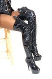Женщина сидя в длинных черных ботинках Стоковое Изображение