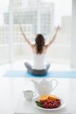 Женщина сидя в позиции раздумья с здоровой едой в переднем плане Стоковое фото RF