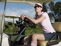 Женщина сидя в тележке гольфа Стоковая Фотография RF