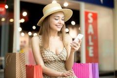 Женщина сидя в торговом центре с усмехаться мобильного телефона стоковые изображения rf