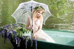 Женщина сидя в шлюпке под зонтиком шнурка Лето Стоковые Изображения RF