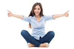 Женщина сидя и показывая большие пальцы руки вверх Стоковые Фотографии RF
