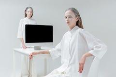 Женщина 2 сидя и стоя около таблицы с компьютером, ПК Стоковое Фото