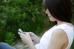 Женщина сидя на внешнем стенде Стоковые Фотографии RF