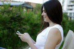 Женщина сидя на внешнем стенде Стоковые Изображения RF