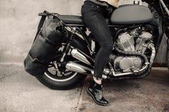 Женщина сидя на его мотоцикле Мотоцикл около гаража Кожаная сумка и джинсы Чернота мотоцикла Ноги ` s женщины Стоковые Фото