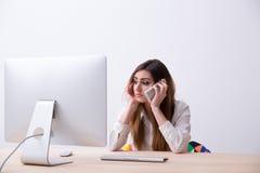 Женщина сидя на ее рабочем месте с smartphone Стоковое Изображение