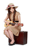 Женщина сидя на ее чемодане пока играющ гитару Стоковое Изображение