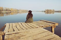 Женщина сидя на деревянной моли Стоковые Изображения