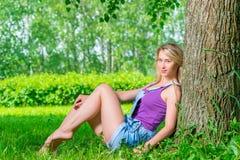 Женщина сидя на зеленой траве в парке Стоковая Фотография RF
