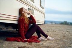 Женщина сидя на красной шотландке около старого фургона на море Стоковые Фото