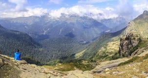 Женщина сидя на краю скалы и смотря на горе l Стоковое Изображение RF