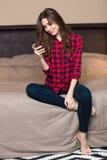 Женщина сидя на кровати и используя smartphone дома Стоковые Фото