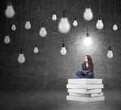 Женщина сидя на куче книг думая о проблеме стоковая фотография rf