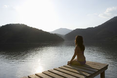 Женщина сидя на моле берега озера на зоре Стоковая Фотография RF