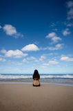 Женщина сидя на песчаном пляже смотря к Horiz Стоковое фото RF
