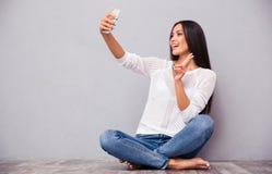 Женщина сидя на поле и делая фото selfie Стоковая Фотография RF