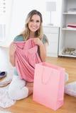 Женщина сидя на поле с новыми платьем и хозяйственной сумкой Стоковое Фото