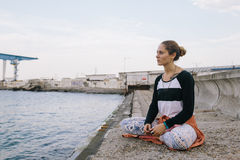 Женщина сидя на представлении йоги на док и смотря вперед к морю Стоковое Фото