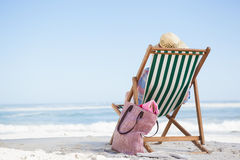 Женщина сидя на пляже в шезлонге Стоковые Фотографии RF