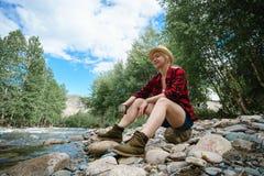 Женщина сидя на речном береге с кружкой в руке Стоковое фото RF