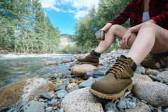 Женщина сидя на речном береге с кружкой в руке Стоковые Фото