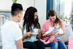 Женщина 3 сидя на софе с младенцем Стоковые Фото