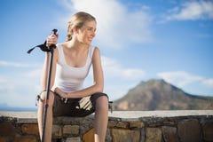 Женщина сидя на стене держа hiking ручка Стоковое Изображение RF