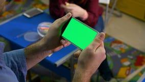 Женщина сидя на столе в комнате класса пока человек наблюдает умный телефон с зеленым экраном видеоматериал