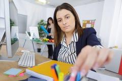 Женщина сидя на столе в офисе стоковое изображение