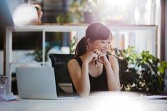 Женщина сидя на столе смотря документы Стоковая Фотография RF
