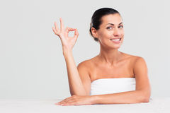 Женщина сидя на таблице в полотенце и показывая одобренный знак стоковые изображения rf