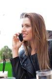 Женщина сидя на таблице говоря на телефоне Стоковые Фотографии RF