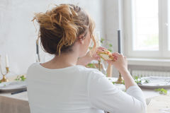 Женщина сидя на таблице есть сандвич Стоковое Изображение RF
