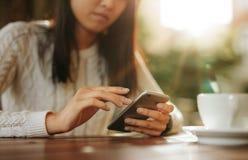 Женщина сидя на таблице используя мобильный телефон Стоковая Фотография