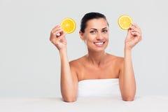 Женщина сидя на таблице и держа апельсин стоковая фотография