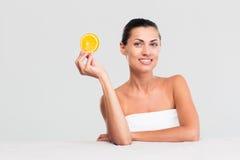 Женщина сидя на таблице и держа апельсин стоковое изображение rf