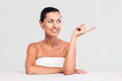 Женщина сидя на таблице и указывая палец прочь стоковое фото