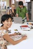 Женщина сидя на таблице при коллеги используя компьтер-книжку в предпосылке Стоковое Изображение RF