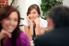 Женщина сидя на таблице ресторана Стоковые Изображения