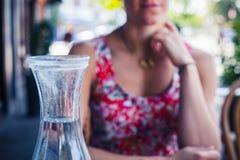 Женщина сидя на таблице с кувшином воды Стоковые Фотографии RF