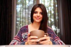 Женщина сидя на таблице с чашкой кофе Стоковая Фотография