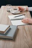 Женщина сидя на таблице с чашкой кофе Стоковые Изображения