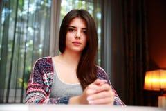Женщина сидя на таблице Стоковое Изображение