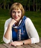 Женщина сидя на таблице outdoors Стоковое фото RF