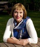 Женщина сидя на таблице outdoors Стоковое Изображение RF