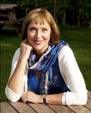 Женщина сидя на таблице outdoors Стоковая Фотография