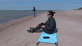 Женщина сидя на циновке разминки около моря сток-видео