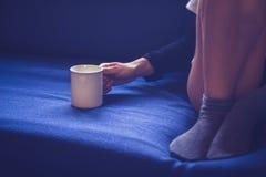 Женщина сидя на чае софы выпивая Стоковая Фотография RF