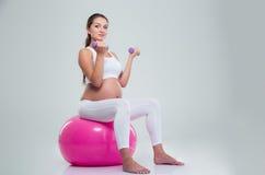 Женщина сидя на шарике и разминке фитнеса с гантелями Стоковое Изображение